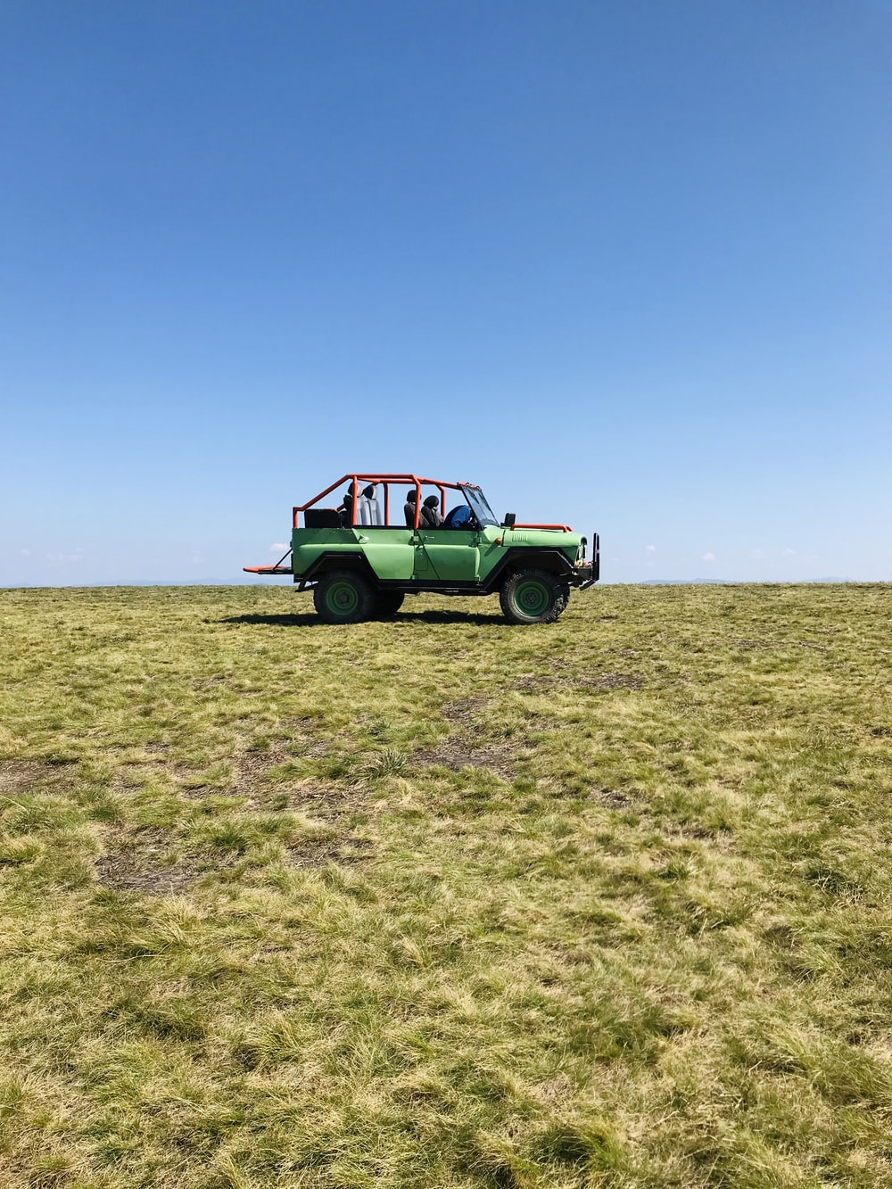 green and white car on green grass field under blue sky during daytime