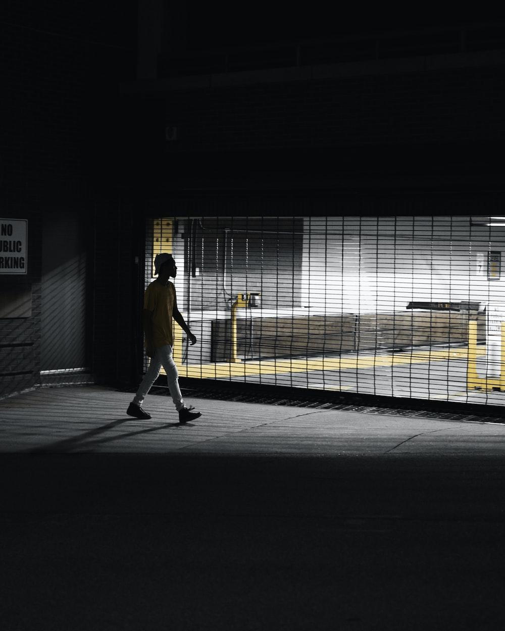 man in yellow jacket walking on sidewalk during daytime