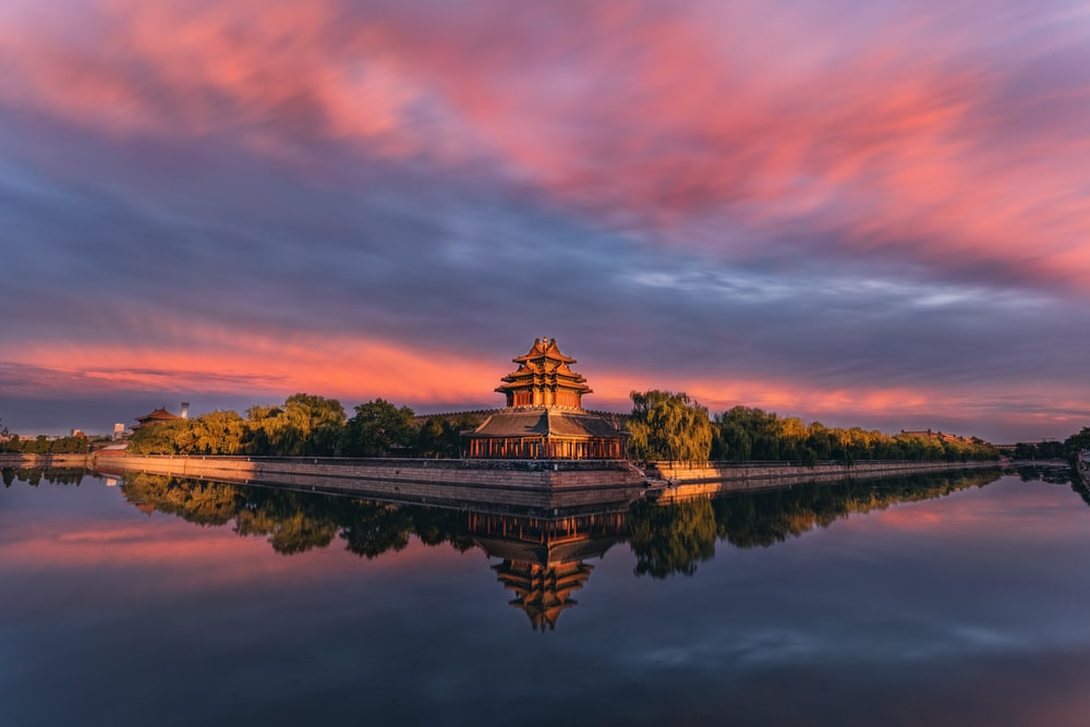 brown and white temple near body of water during sunset