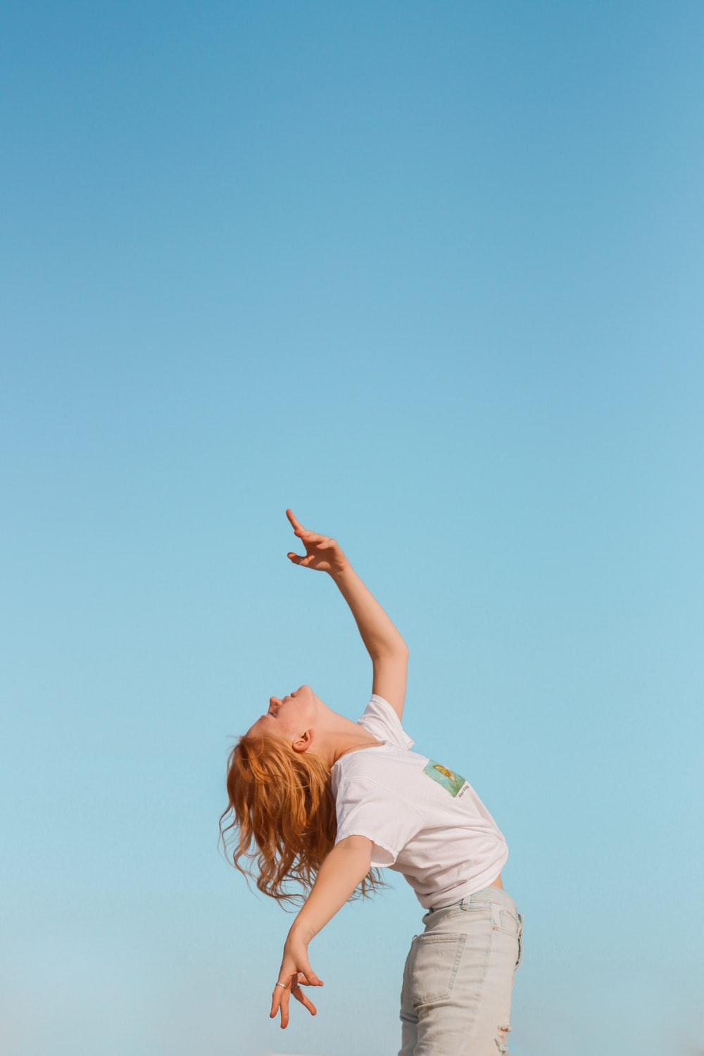 woman in white t-shirt raising her hands
