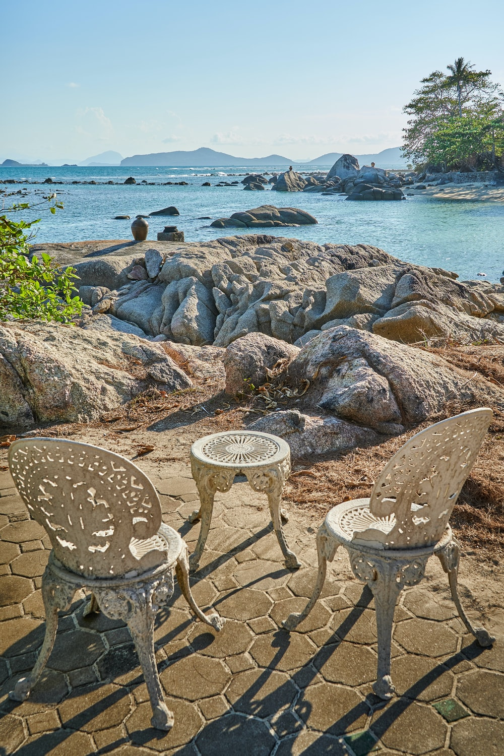 white round table on rocky shore during daytime