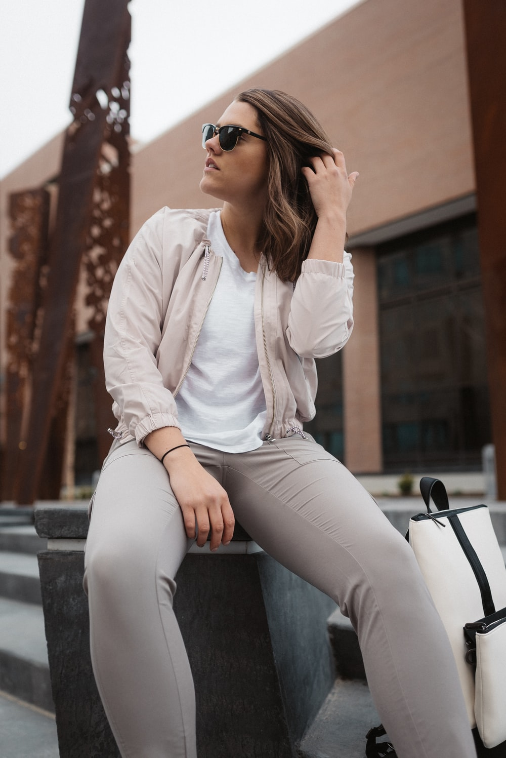 woman in white long sleeve shirt and gray pants sitting on gray concrete bench during daytime