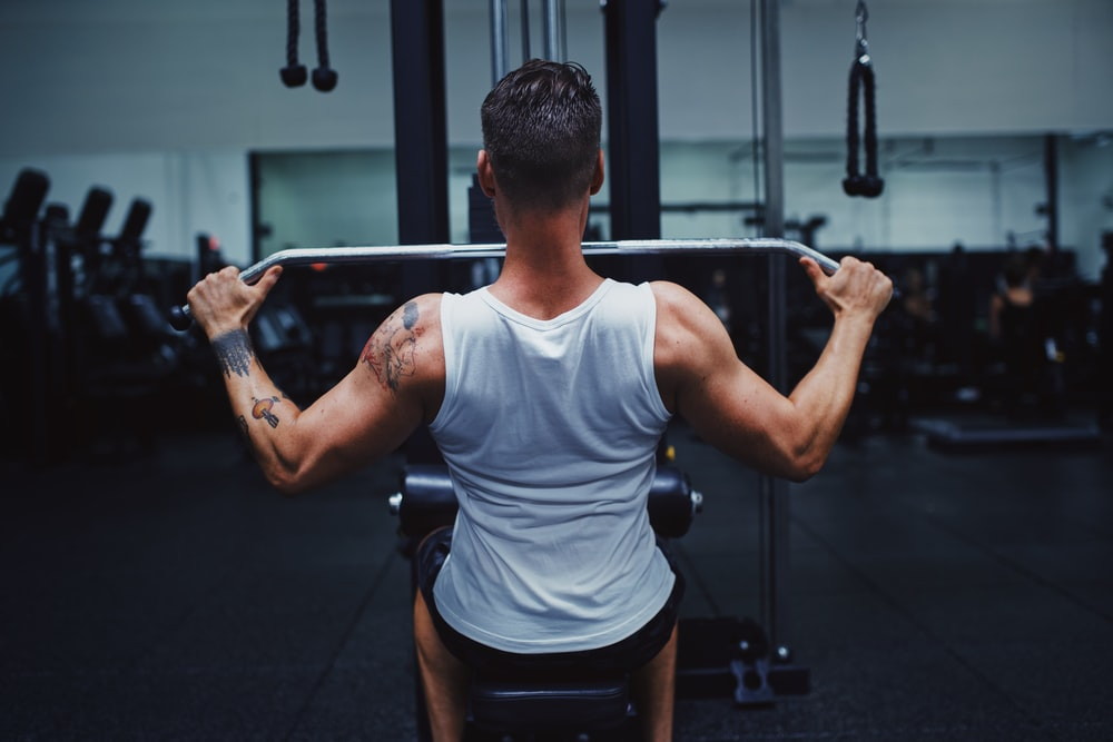 man in gray tank top and black shorts holding black barbell
