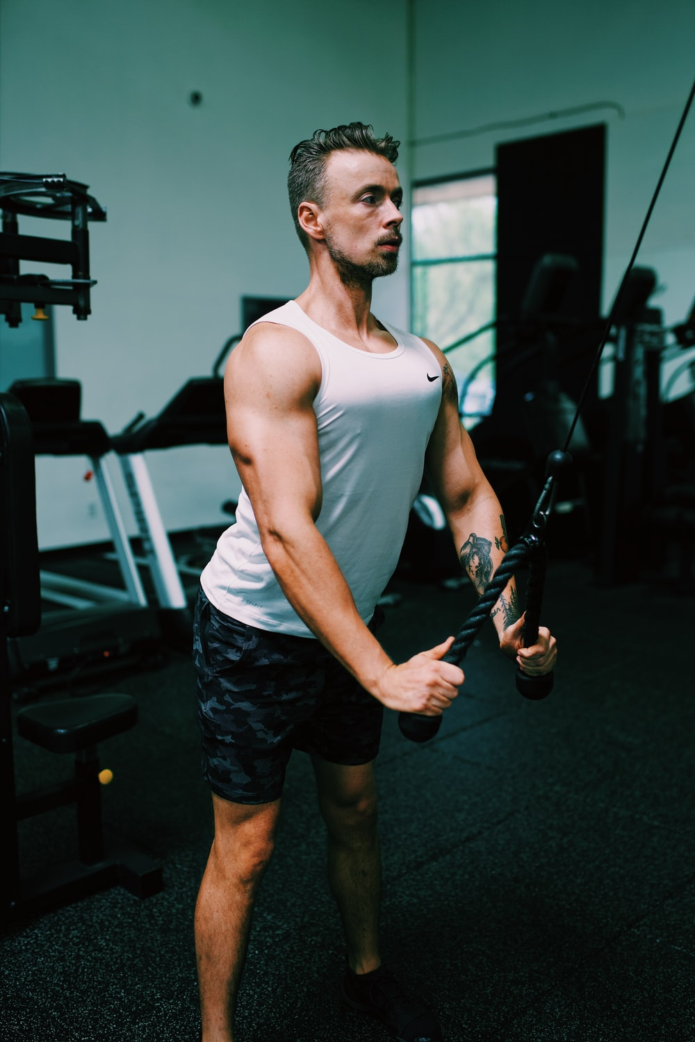 man in white tank top and black shorts holding black and brown rifle
