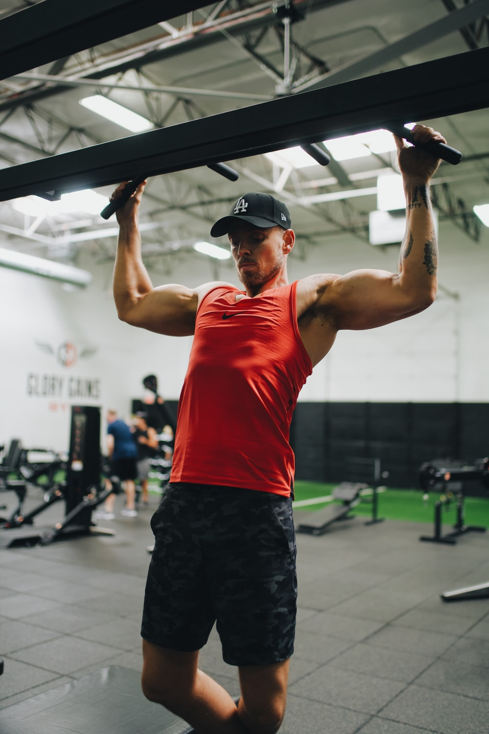 man in red tank top and black shorts holding black exercise equipment