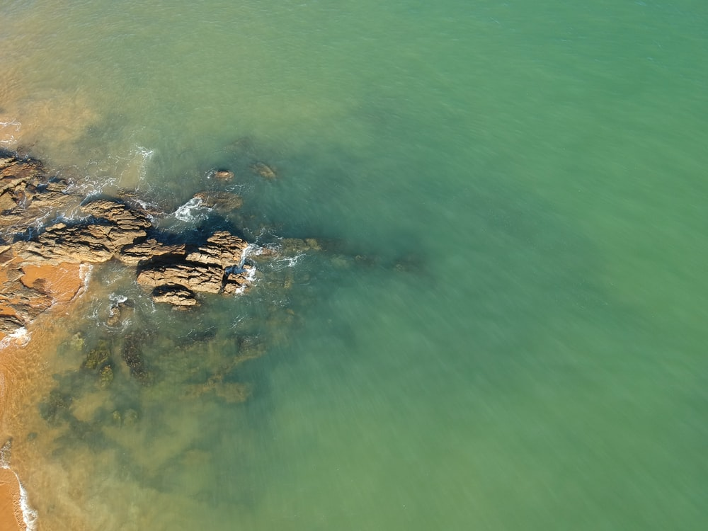 brown rock formation on body of water during daytime