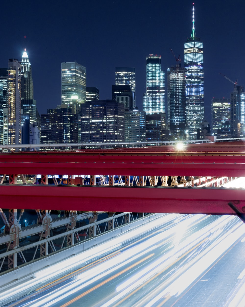 red bridge over city skyline during night time
