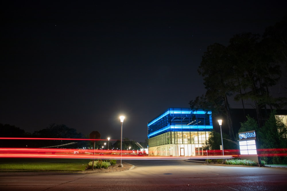 blue and white building near green trees during night time