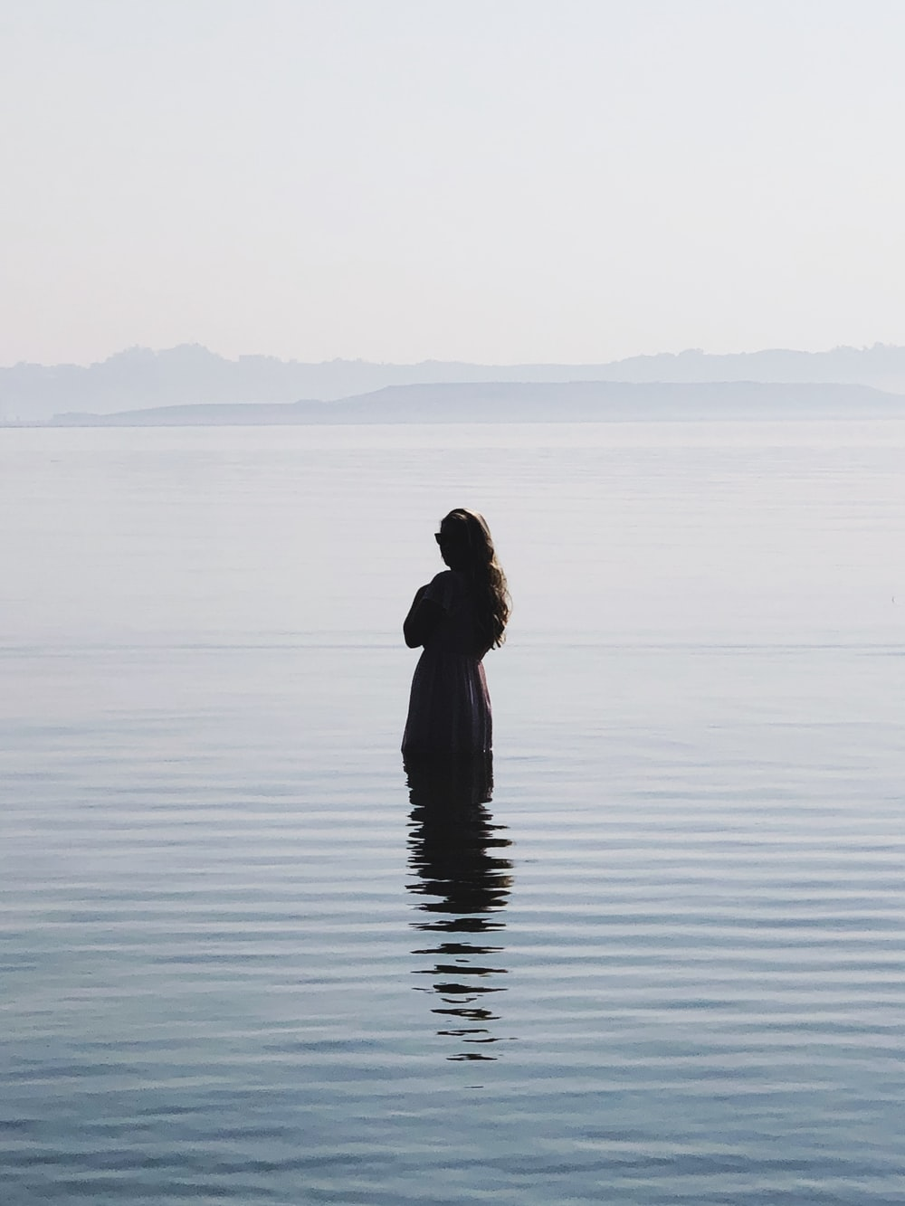 woman in black dress standing on water during daytime