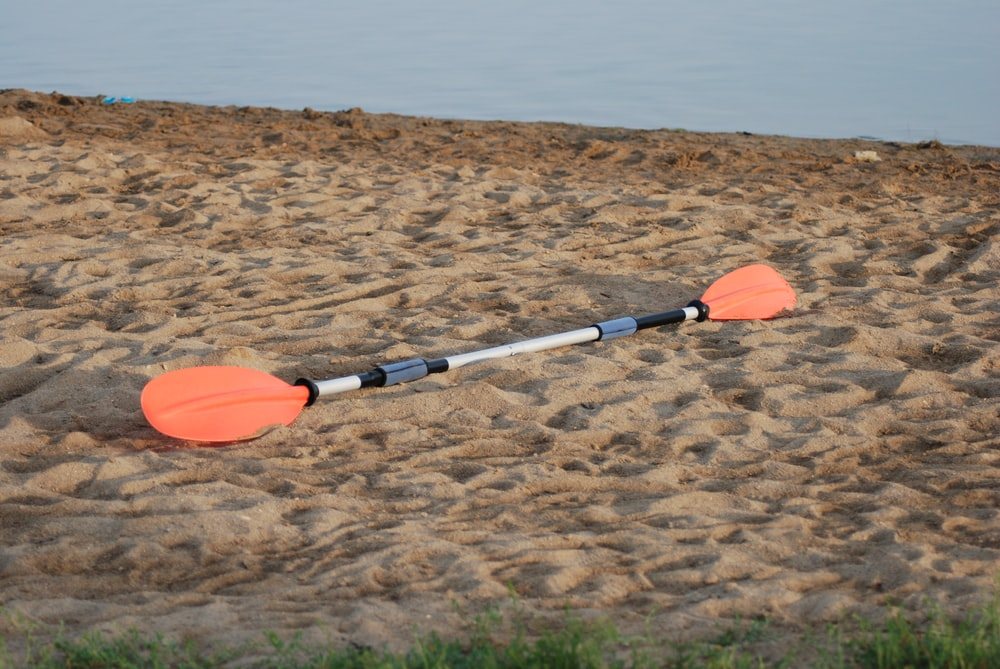 orange and white hand tool on brown sand