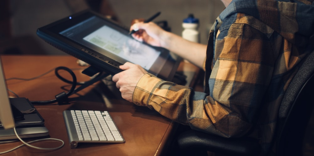 person in brown and black plaid long sleeve shirt using black laptop computer