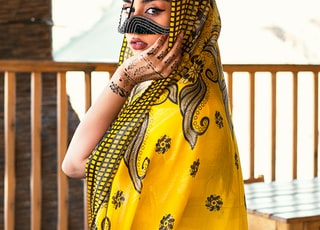 woman in yellow and black floral hijab standing near brown wooden fence during daytime