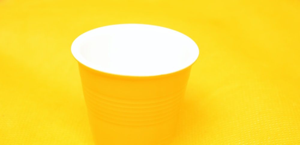 yellow plastic cup on orange surface