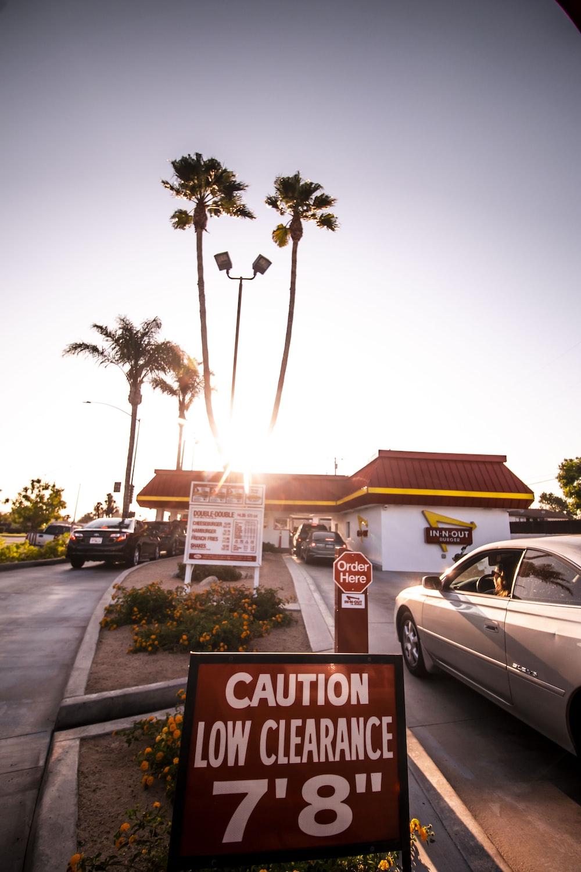 white sedan parked near palm trees during daytime