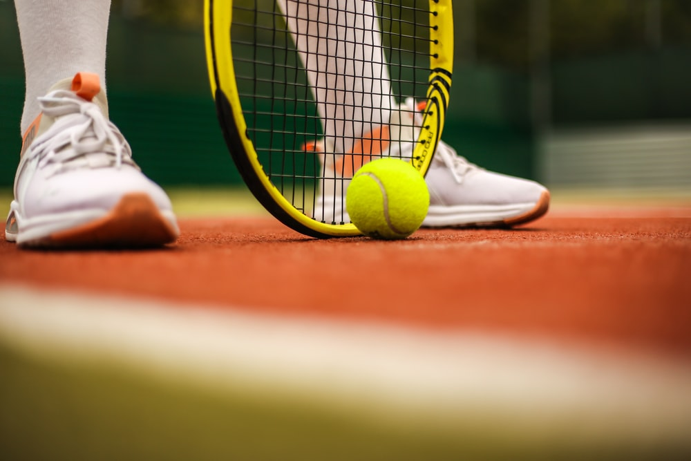 person in white nike sneakers playing tennis