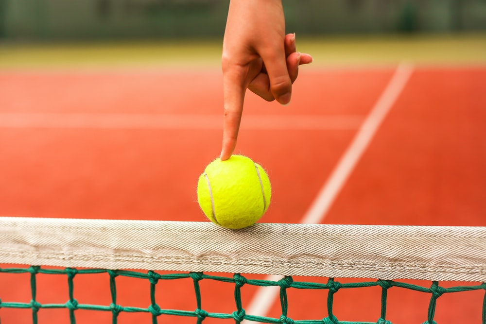 person holding yellow tennis ball on red and white net