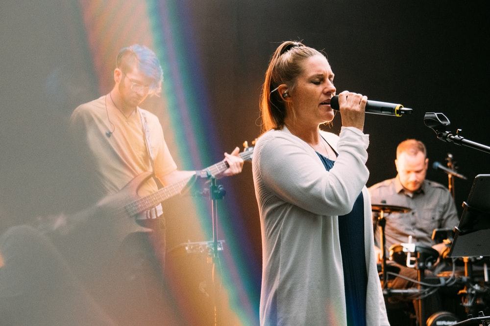 woman in white long sleeve shirt singing