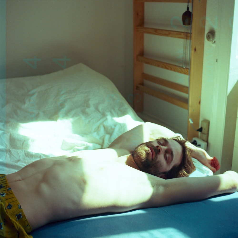 topless man lying on bed