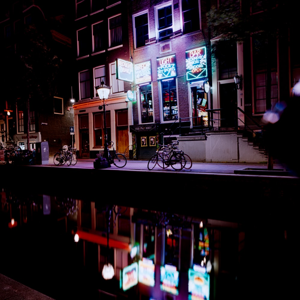 black bicycle parked beside building during night time