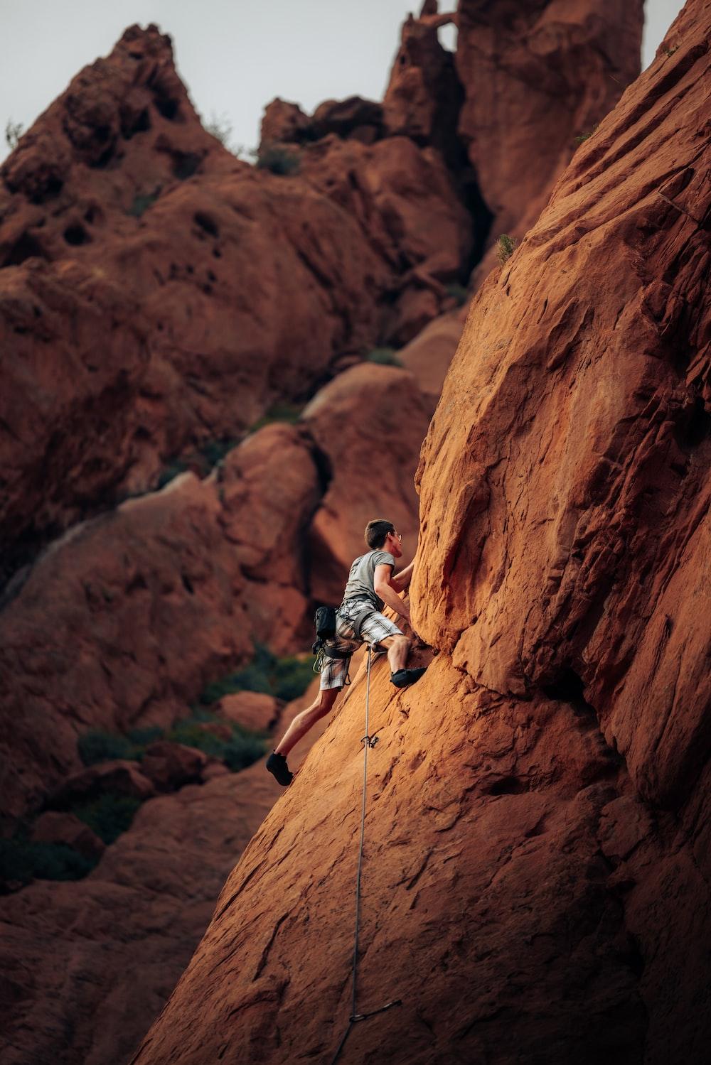 man in white shirt climbing brown rock mountain during daytime