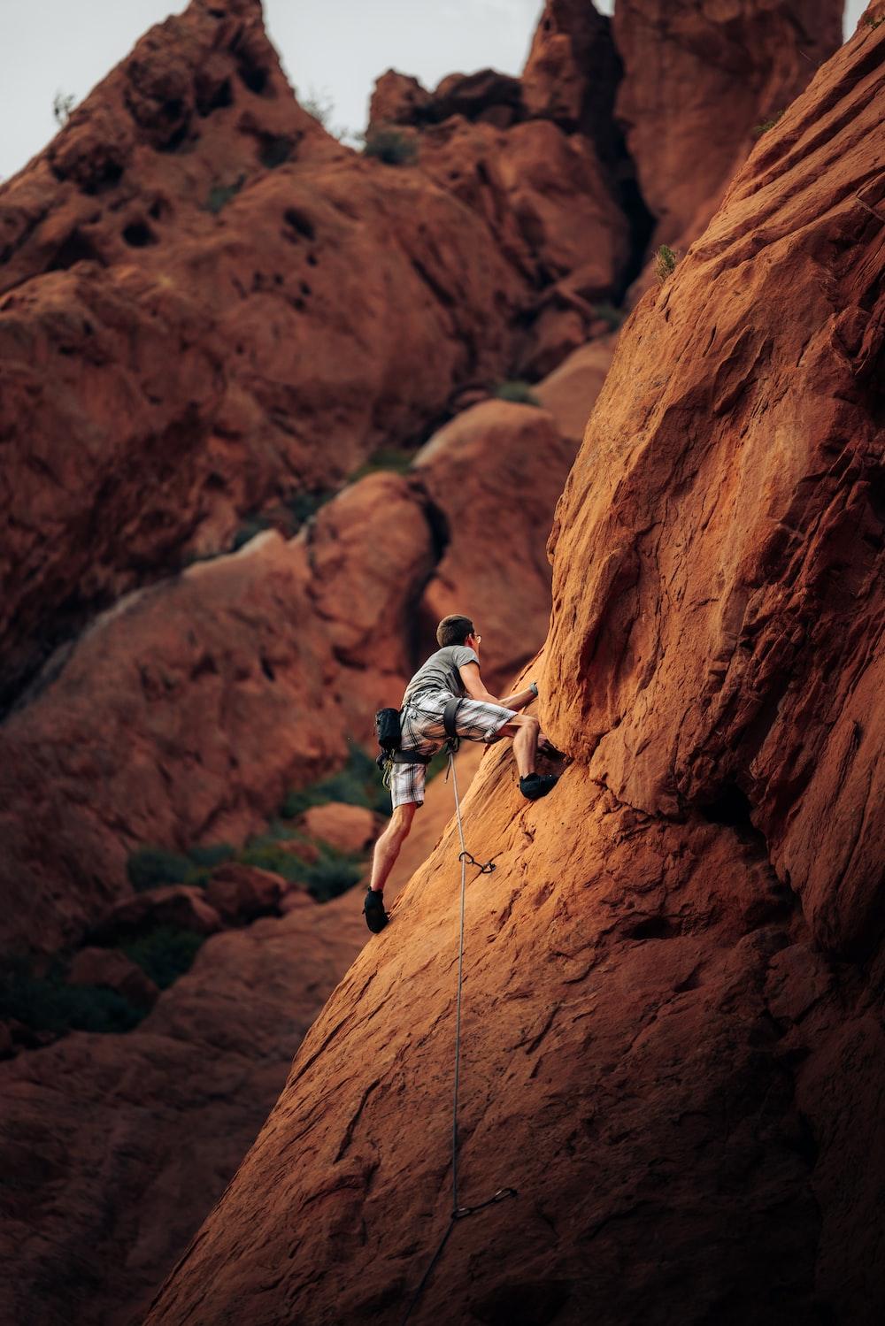 man in white t-shirt climbing brown rock mountain during daytime