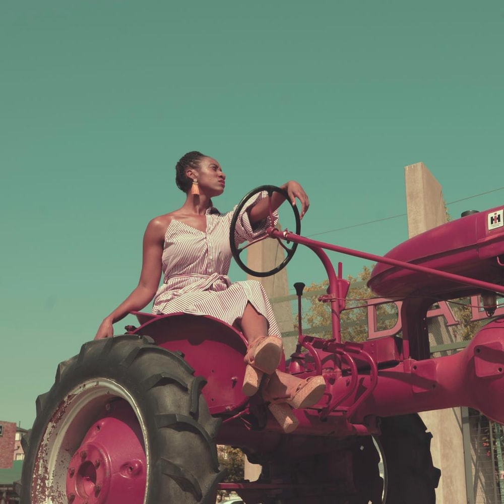 woman in white tank top riding red tractor during daytime