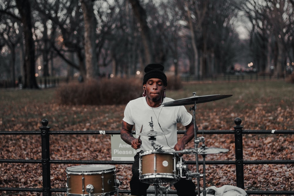 man in white crew neck long sleeve shirt and black cap standing beside drum set during