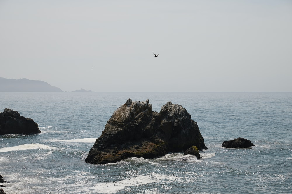 person in yellow shirt jumping on rock formation near body of water during daytime