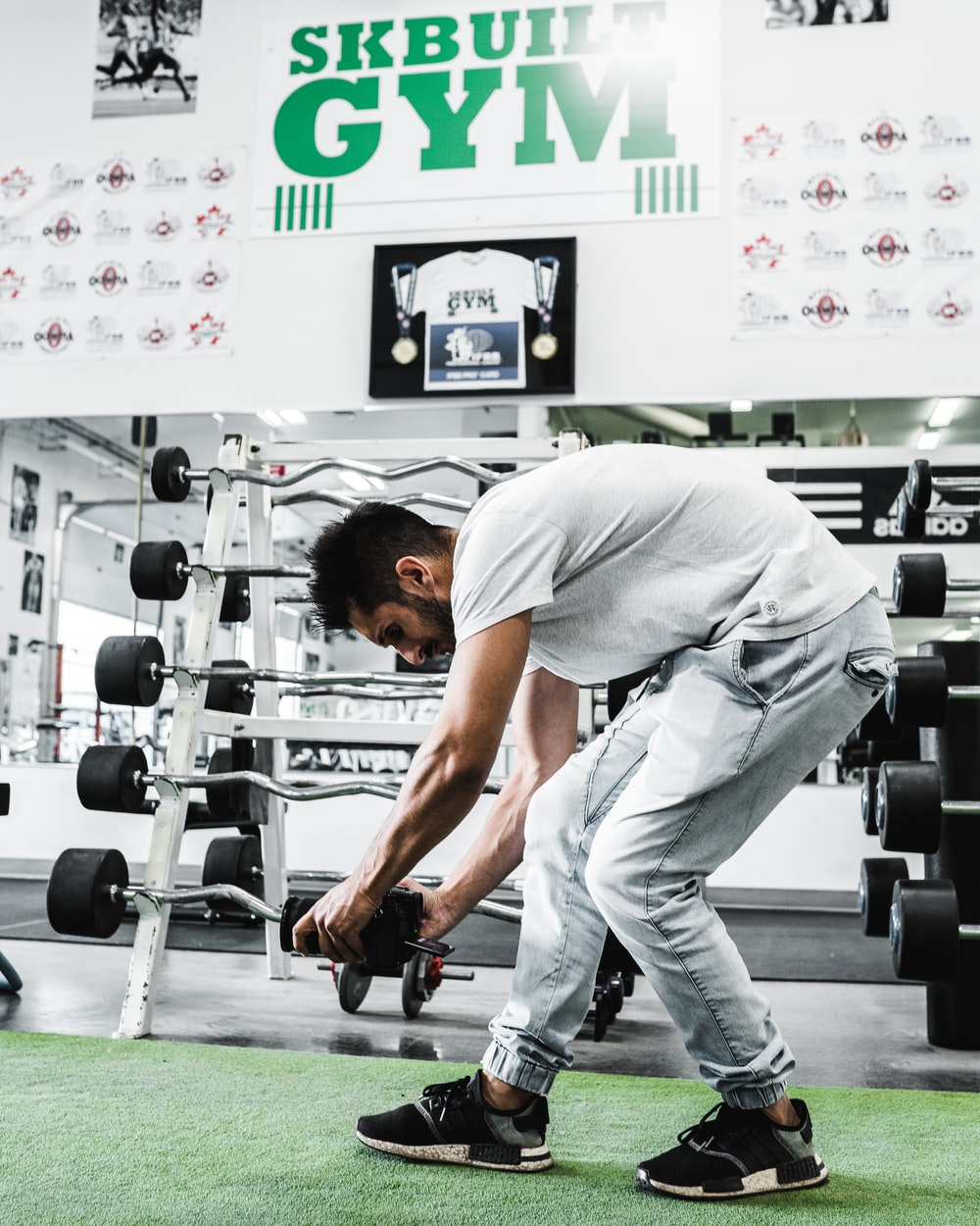 man in white t-shirt and white pants holding black and gray dumbbell