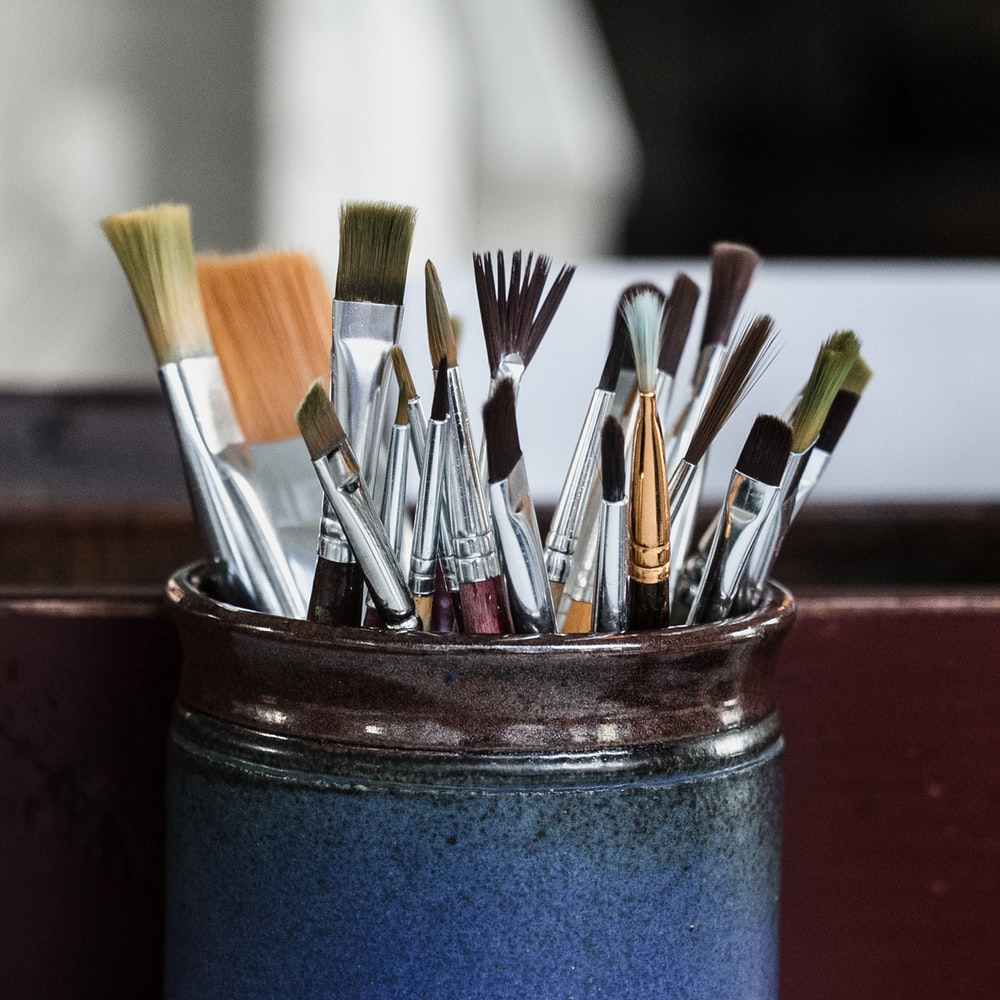 paint brushes in blue container