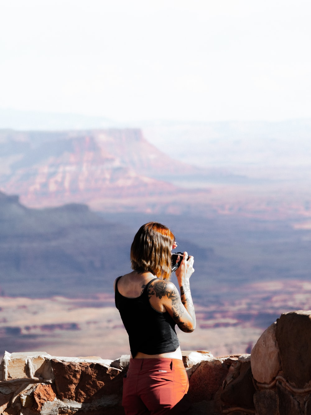woman in black tank top sitting on rock formation during daytime
