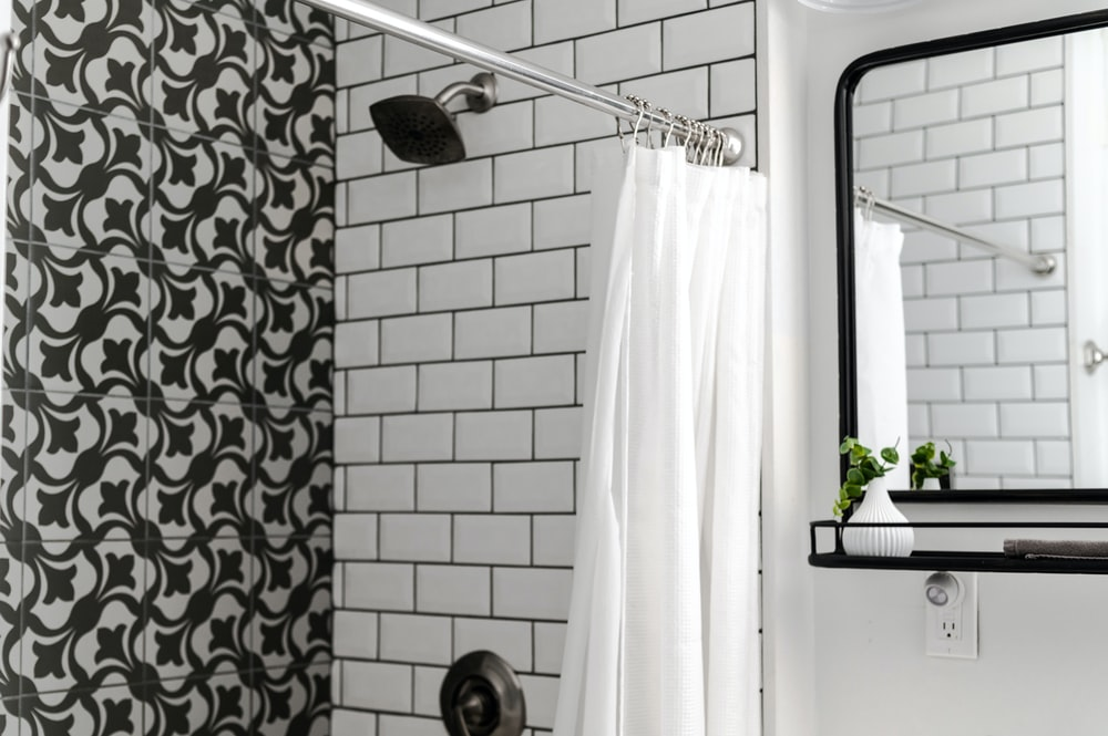 white shower curtain on stainless steel shower head