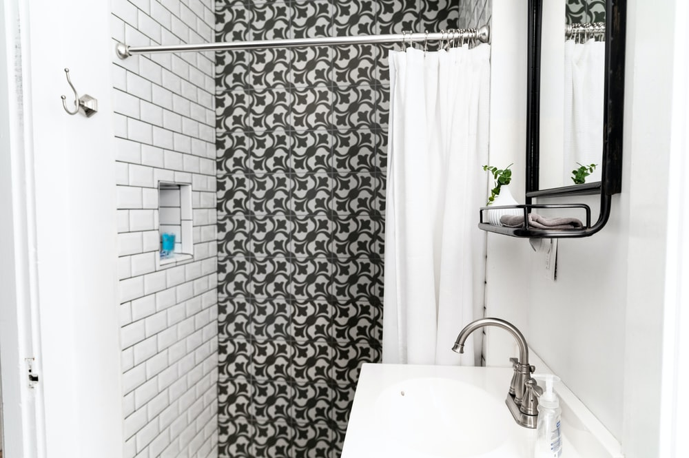 white ceramic sink beside white and gray floral shower curtain