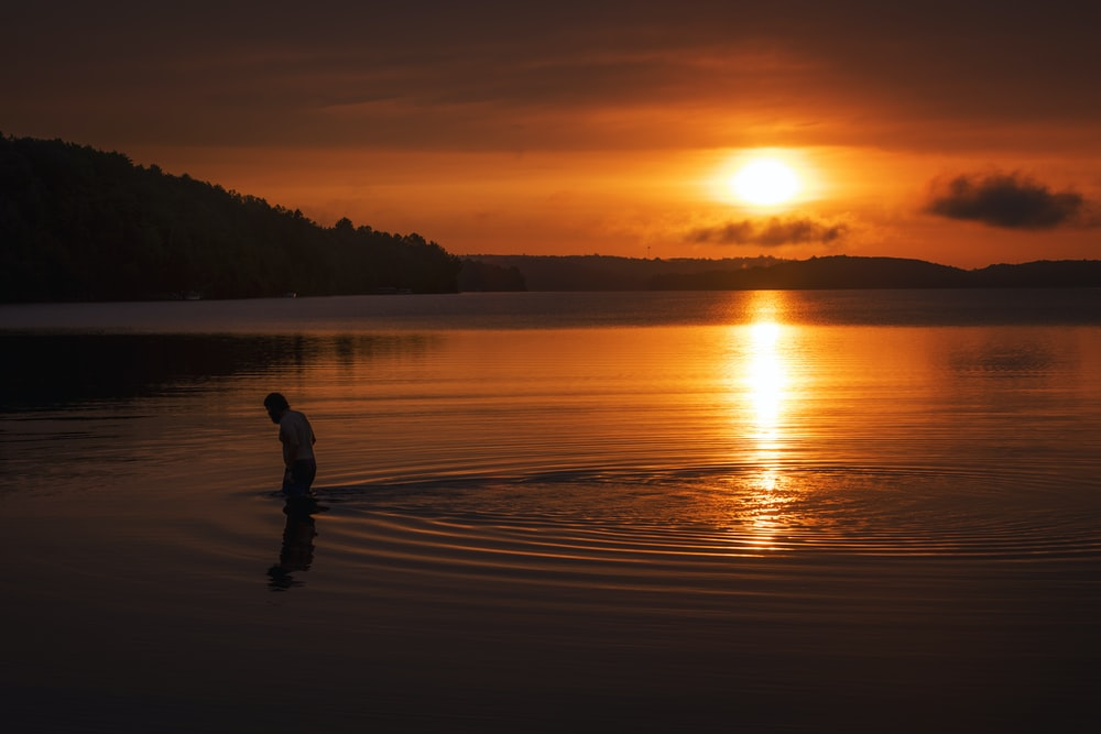 silhouette of person standing on body of water during sunset
