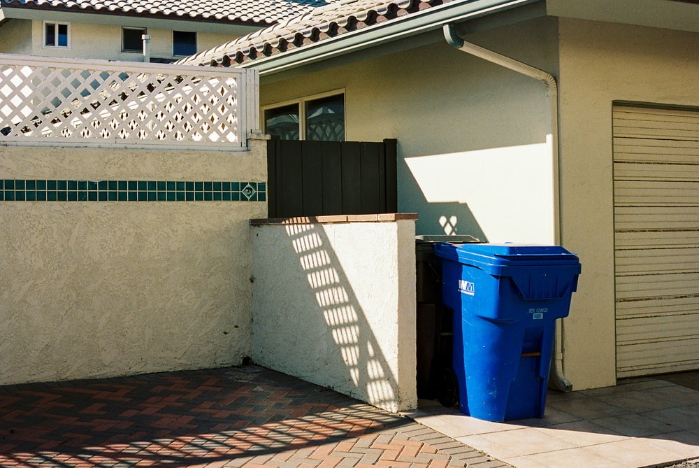 blue trash bins beside white wall