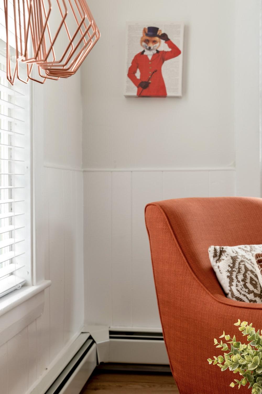 brown and white throw pillow on orange sofa chair