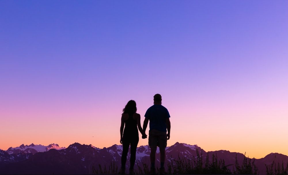 silhouette of 2 men standing on mountain during sunset
