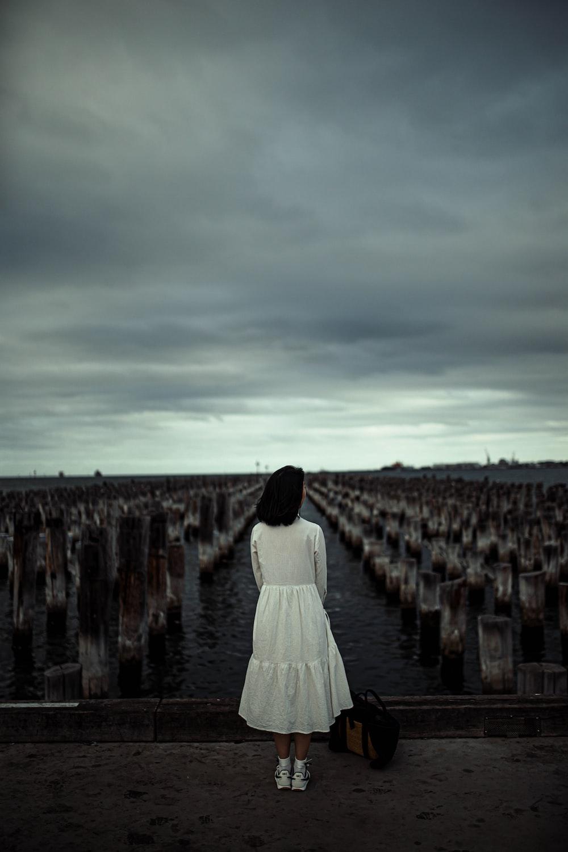 woman in white dress walking on brown wooden dock during daytime