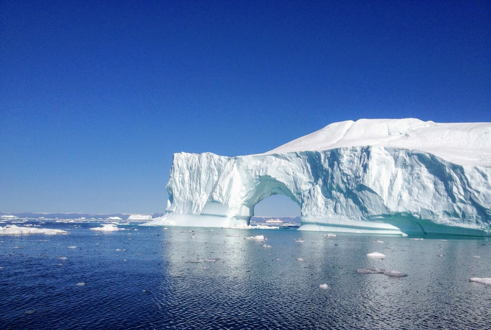 white ice formation on blue sea under blue sky during daytime