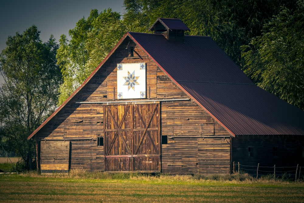 brown wooden barn on green grass field during daytime