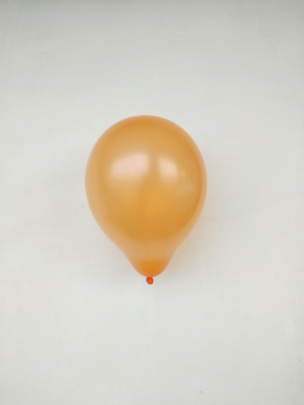 yellow balloon on white surface