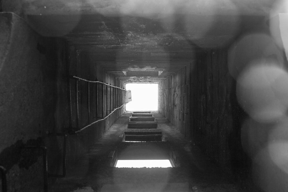 grayscale photo of tunnel with light