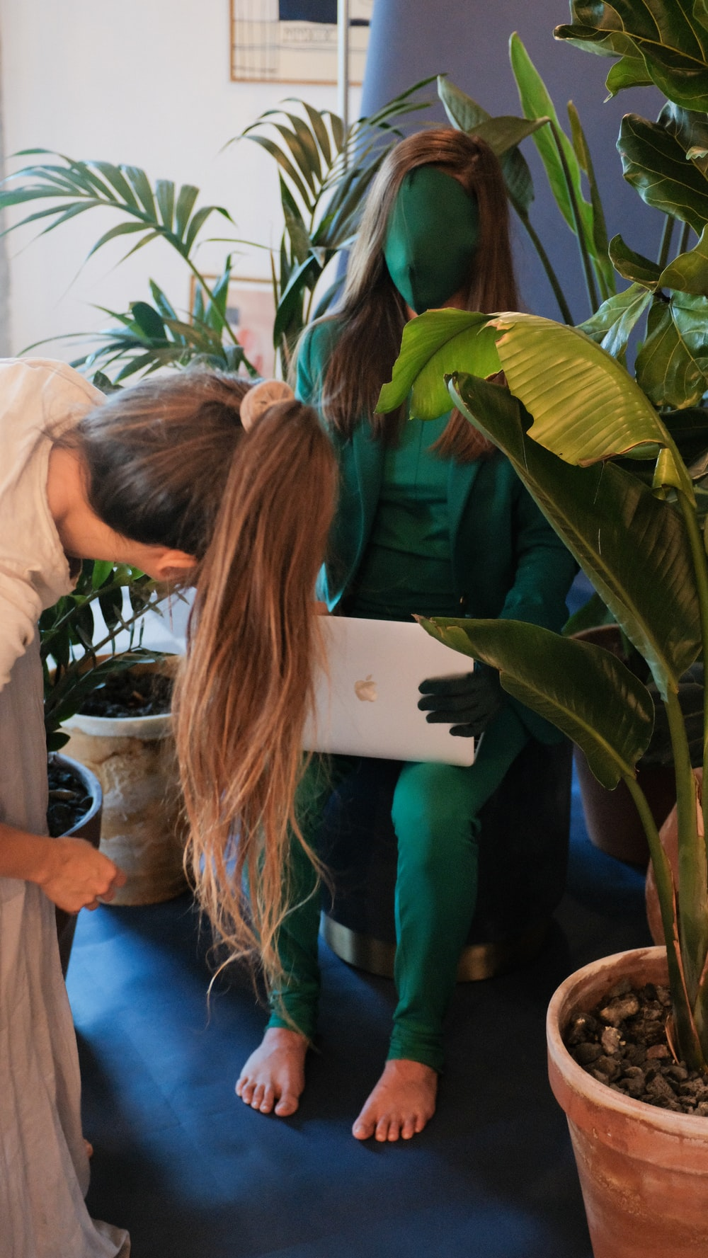 woman in green shirt standing beside green plant