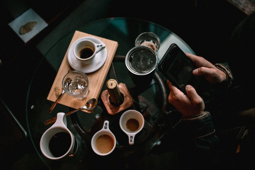person holding black smartphone near white ceramic mug on table