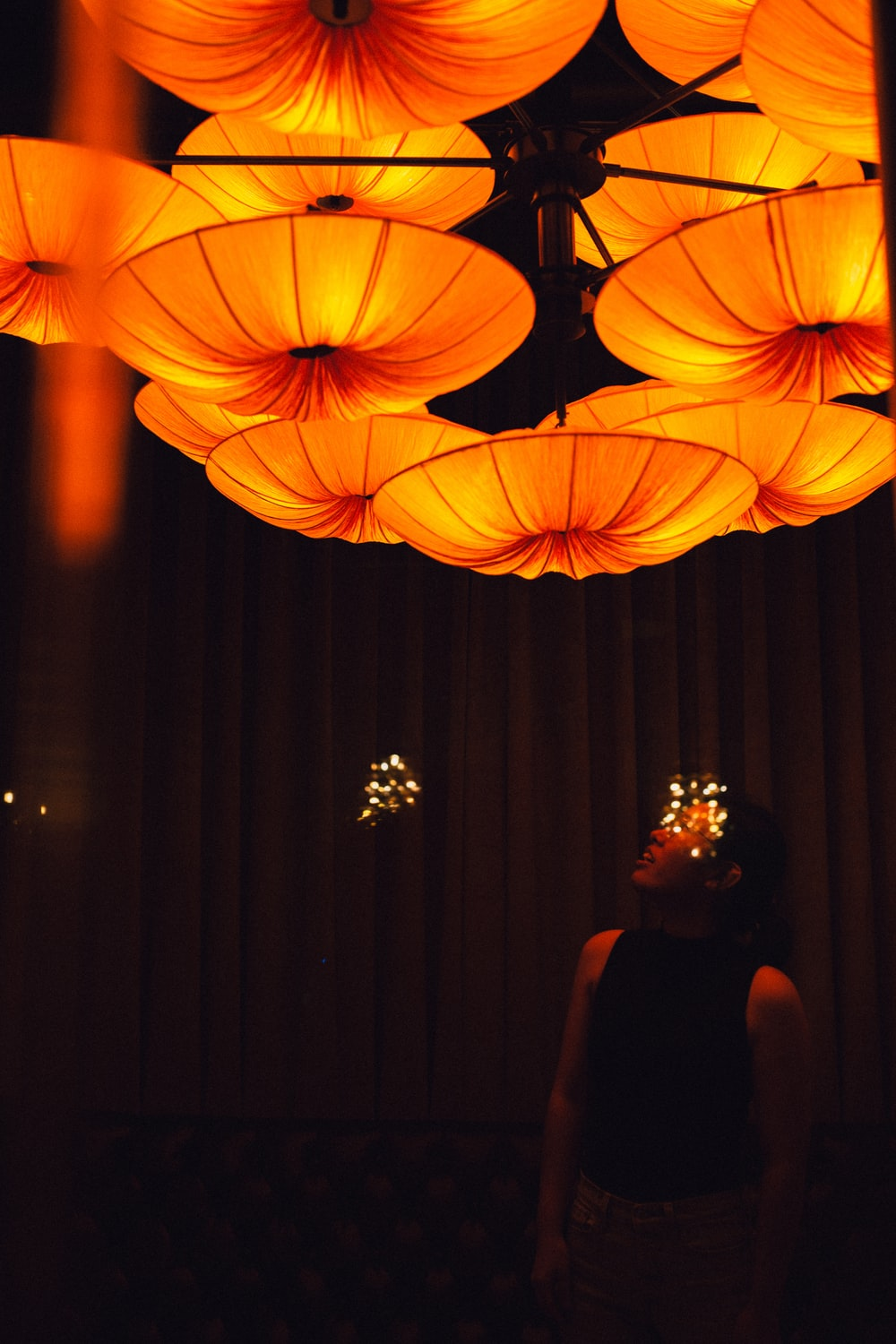 woman in black dress standing near red string lights