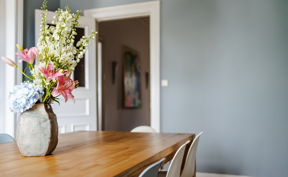 white and pink flower bouquet on brown wooden table