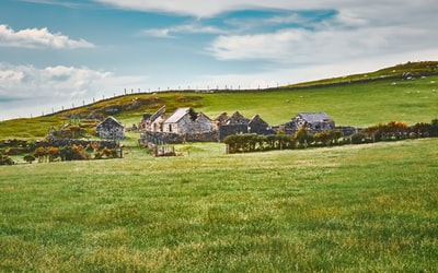 white and gray house on green grass field under white clouds and blue sky during daytime farmhouse zoom background
