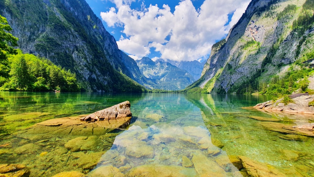 green mountains beside body of water under blue sky during daytime
