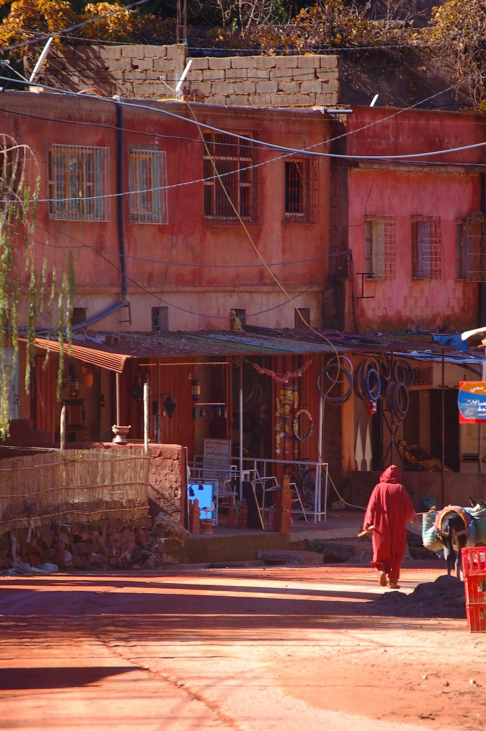 man in red jacket walking on sidewalk during daytime