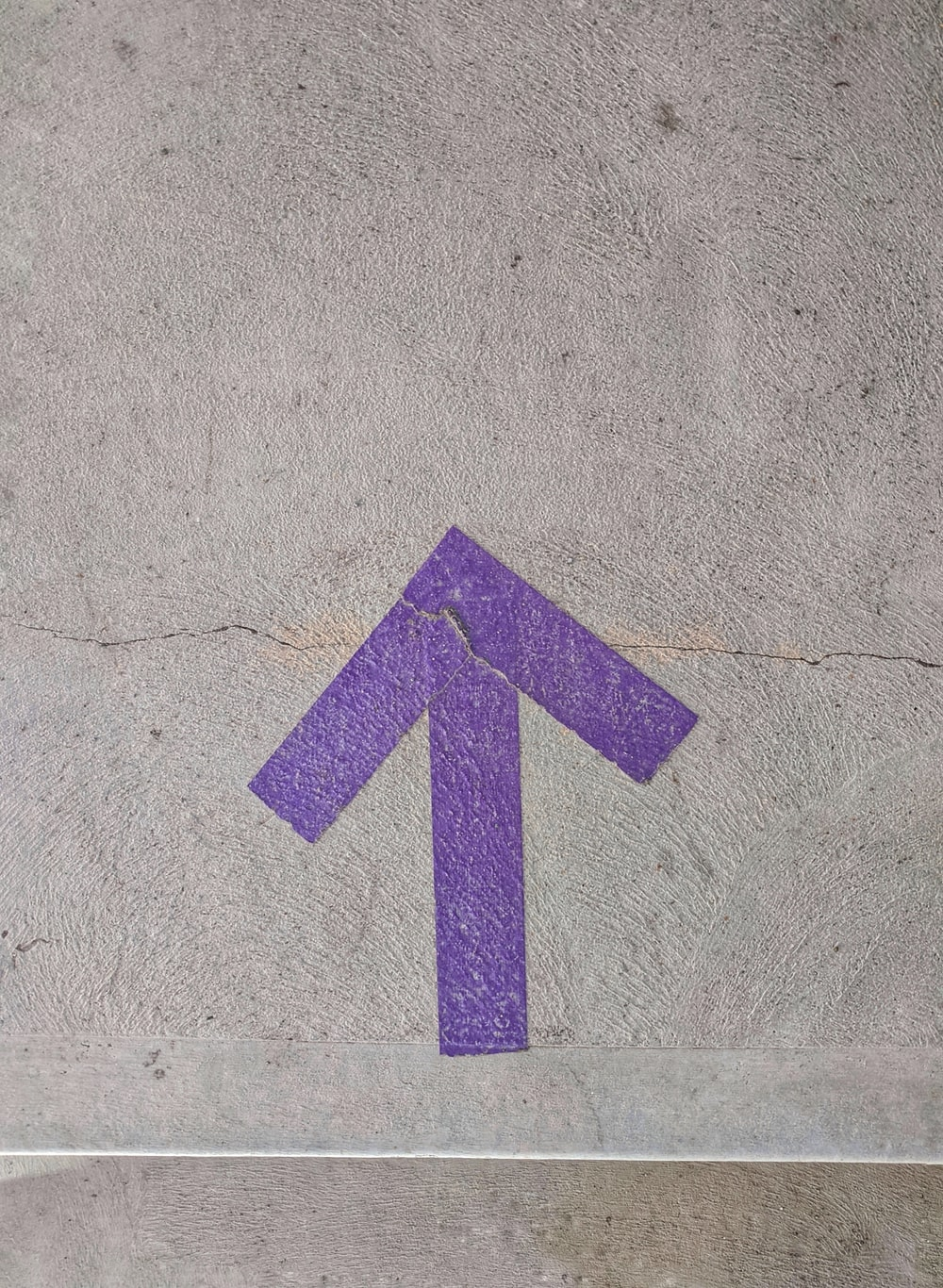 purple and white arrow sign